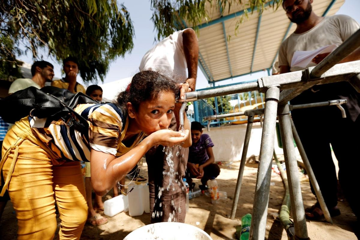 A young girl drinks water from an Oxfam tap stand.