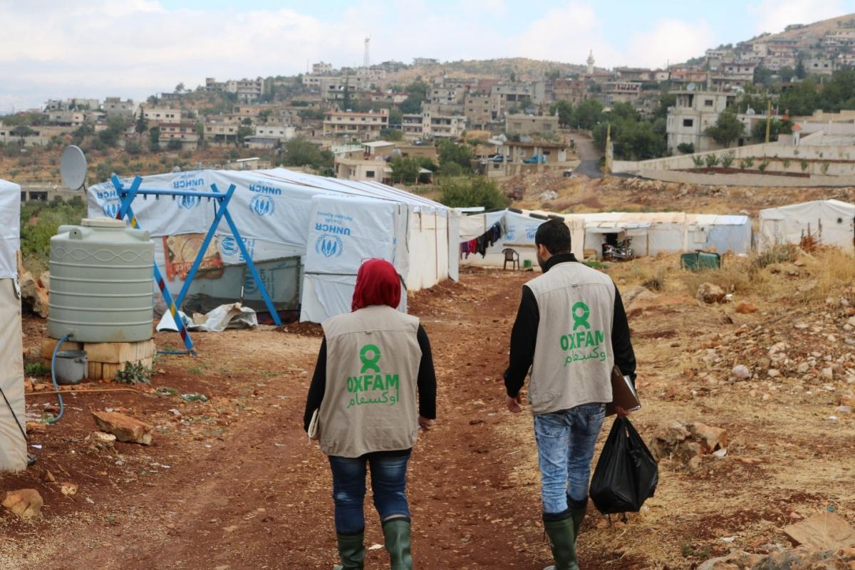 Oxfam staff walking towards Sawere, a Syrian refugee settlement in Lebanon's Bekka Valley.