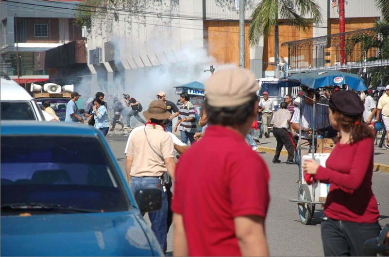 Water cannon tank coming through the cloud of tear gas in San Pedro Sula on Election Day, 2013